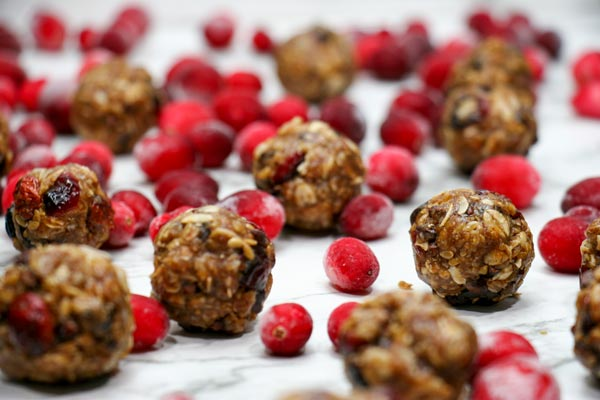 scattered cranberry oatmeal cookie energy bites with fresh frozen cranberries on white marble counter