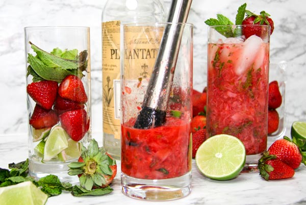 strawberries and mint muddled in highball glass with finished strawberry mojito on one side and ingredients on the other