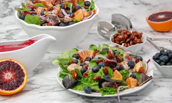 spring salad mix with blueberries, blood oranges, and candied almonds with nearby raspberry orange vinaigrette