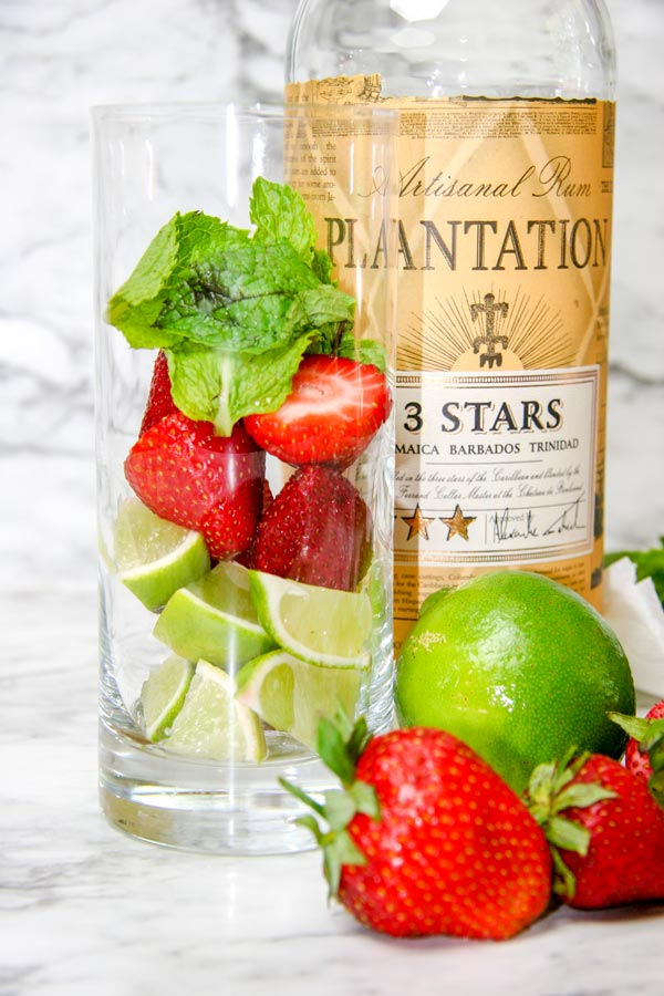 highball glass with strawberries, limes, and mint next to plantation white rum