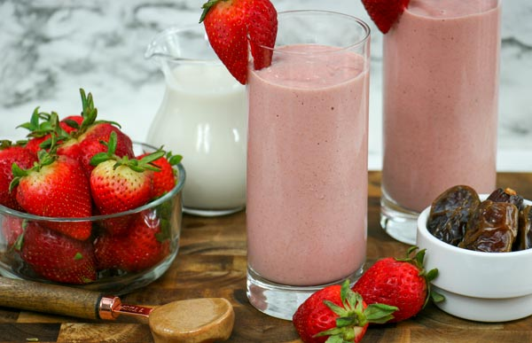 two frozen strawberry smoothies with medjool dates and fresh strawberries in nearby bowls, almond butter on measuring spoon, and almond milk in small pitcher