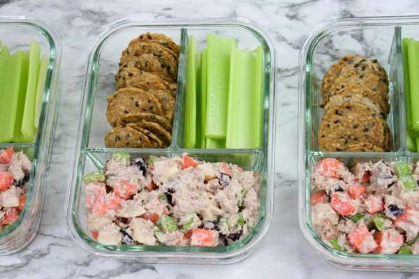 three bento boxes lined up in a row, each with celery sticks, seed crackers, and healthy sweet and crunchy tuna salad