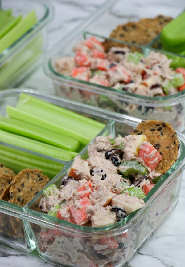 three bento lunch boxes of crackers, celery, and fresh healthy veggie packed tuna salad with apples and cranberries