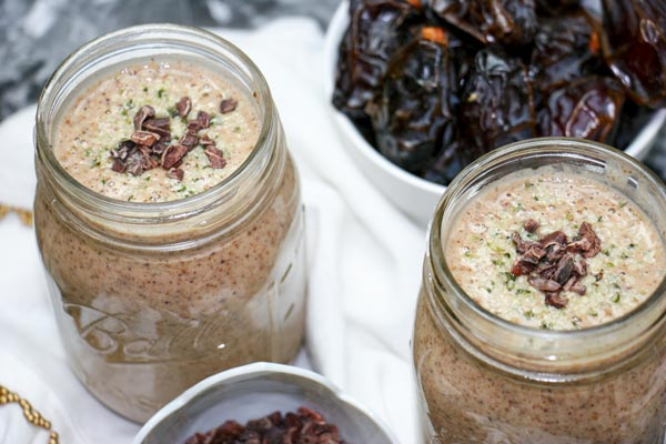 two banana date smoothies in jars with bowl of medjool dates