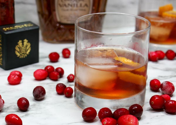 rocks glass of vanilla cranbery whiskey cocktail with fresh cranberries around it