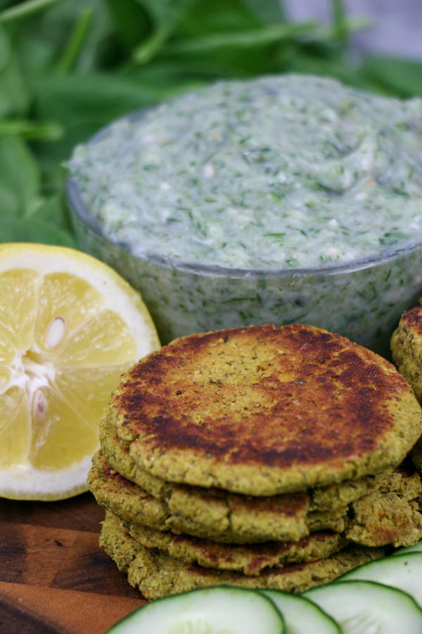 one stack of spinach falafel with vegan tzatziki sauce and sliced cucumbers and lemon