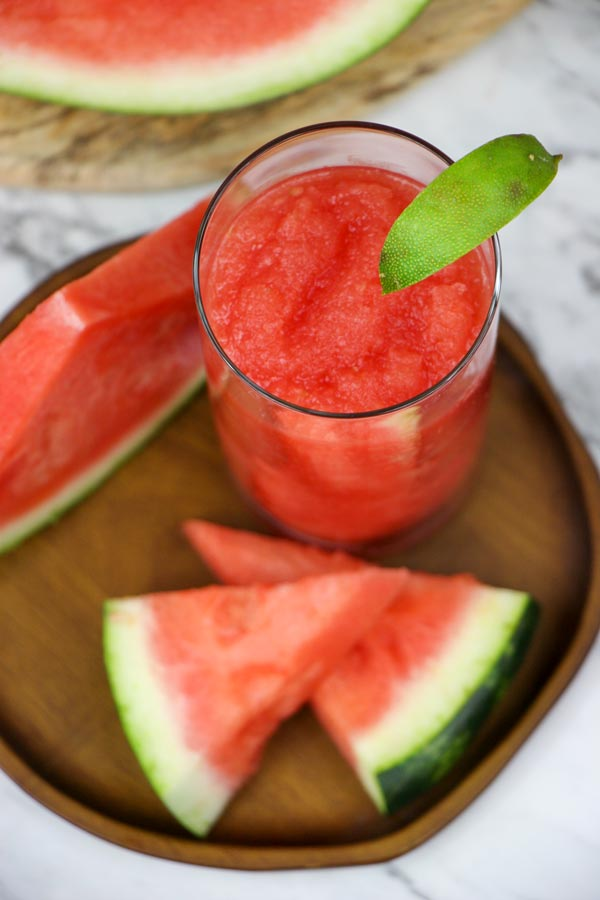 top down view of a glass of watermelon rum slush garnished with a lime wedge and on a plate with watermelon wedges next to it
