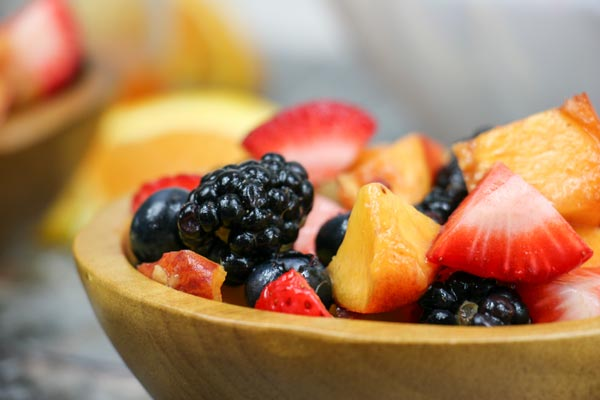 close up of a wooden bowl of summer fruit salad tossed in a sweet and spicy dressing